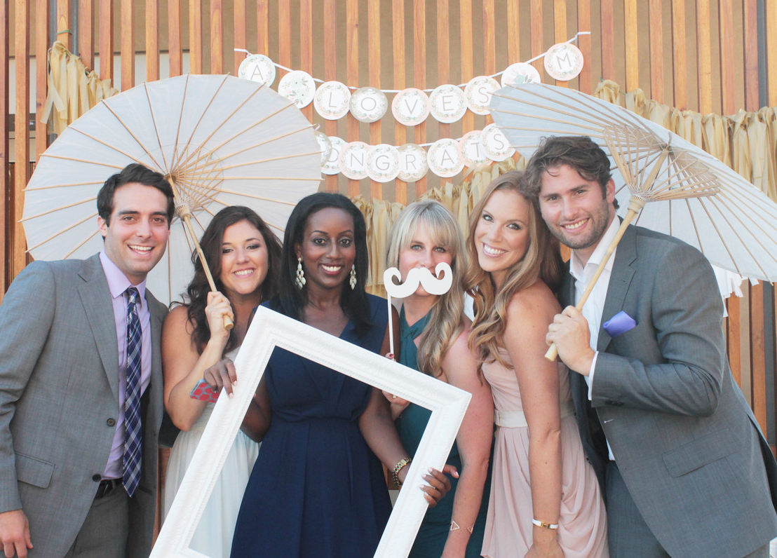 Wedding Guests Pose with Props in Front a Custom Garland